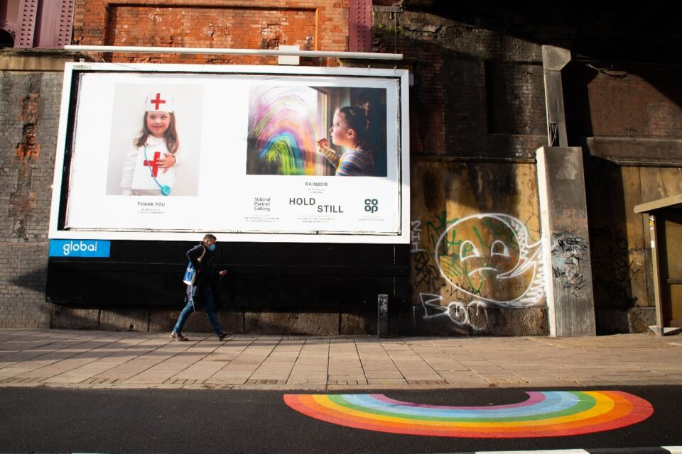 An outdoor billboard featuring two images part of the Hold Still Community Exhibition. A man walks passed the billboard