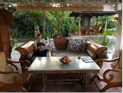 Woman reading, sitting on the left side of a lounge chair on a covered verandah