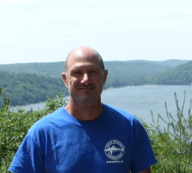Portrait shot Caucasian man wearing blue t shirt. Background is lake and forests